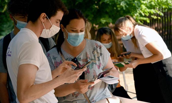 Nhân viên tháp Eiffel kiểm tra giấy chứng nhận tình trạng y tế của khách tham quan ở thủ đô Paris, Pháp hôm 21/7. Ảnh: AFP.